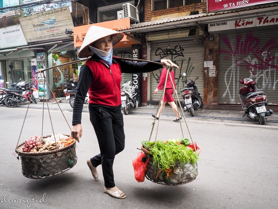 street hawkers in hanoi - a woman with her traditional carry tool