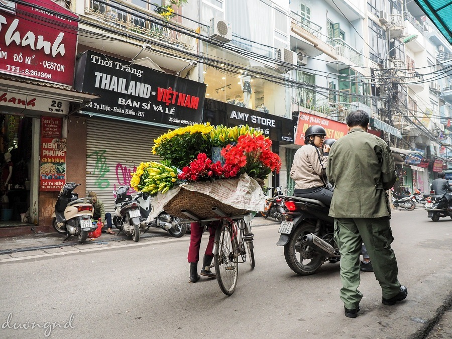 street hawkers in hanoi - the colorful bouquets brighten the whole street